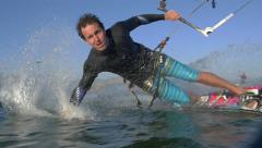 SLOW MOTION: Young kiteboarder riding toeside - stock footage