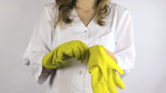 Woman in white robe smock put on yellow rubber gloves on hands - stock footage