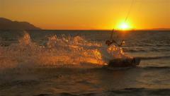 SLOW MOTION: Kitesurfer splashing the water at sunset Stock Footage