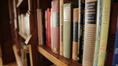 Sliding shot of books on a bookshelf Stock Footage