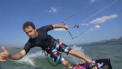 SLOW MOTION: Kiteboarder doing shaka sign into camera - stock footage
