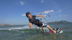 SLOW MOTION: Kiteboarder shows shaka sign while riding Stock Footage