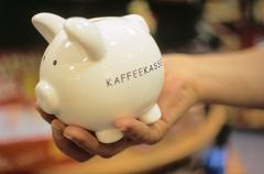 Woman hand holding a piggy bank with the writing kaffeekasse coffee cash box Stock Photos