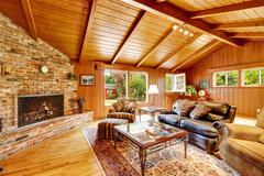 luxury log cabin house interior. living room with fireplace and leather couch - stock photo
