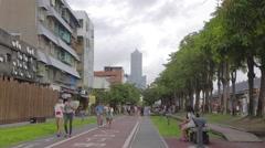 West coast bike path - people walking in front of building 85 Stock Footage