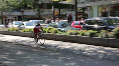 Man riding bike in downtown ahead of traffic Stock Footage