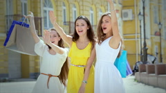 Three girls waving and attract attention holding shopping bags with fashion - stock footage