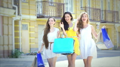 Three girls on a sunny afternoon walk with bags fashion shopping slow motion Stock Footage