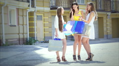 Shopaholic girls looking at shopping and then start to go merrily waving package - stock footage