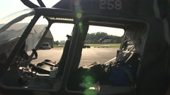 Military helicopter sits while a police helicopter takes off Stock Footage