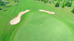 Flying over golf hole with flag Stock Footage