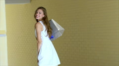 Young cheerful girl-shopaholic posing with shopping - stock footage