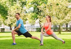 Smiling couple stretching outdoors Kuvituskuvat