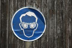 Dented blue sign on wooden door, eye protection needed Stock Photos