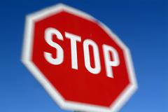 zoomed, blurry, unfocused stop sign, austria - stock photo