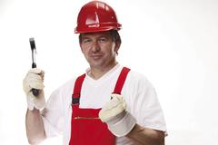 Tradesman wearing red hardhat, his fist clenched, holding a hammer in his oth Stock Photos