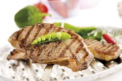 rump steaks on an aluminum grill, grill marks, garnished with pea pod and pep - stock photo