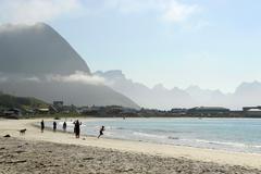 people at ramberg beach, lofoten archipelago, norway, scandinavia - stock photo