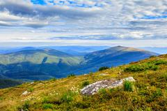 Mountain panorama with large rock on the hillside Stock Photos