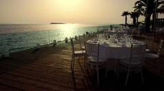 Luxurious formal dinner table outdoors at sunset with sea view Stock Footage