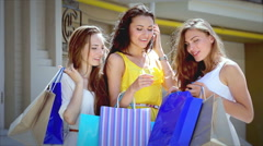 Three cute girls discuss their shopping outside the boutique Stock Footage
