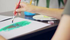 Girl painting in the room, using a palette, art, camera movement - stock footage