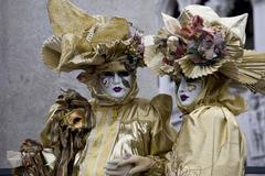two golden costumes and masks, carnevale di venezia, carneval in venice, ital - stock photo
