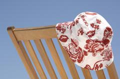 Sun hat placed on a wooden deck chair, diffushi island, holiday island, south Stock Photos