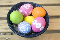Hand-painted easter eggs in a blue bamboo bowl Stock Photos