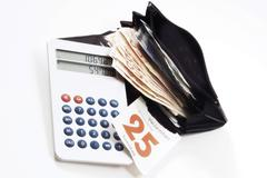 Christmas spending: wallet with cash, calculator and a calendar page marking  Stock Photos