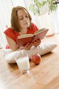 Stock Photo of woman lying on the parquet floor and reading a book