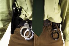Detail, female police officer with handcuffs and gun holster Stock Photos