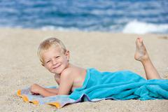 Four-year-old boy relaxing on the beach Stock Photos