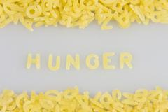 """""""hunger"""" spelled out in noodle letters, pasta alphabet Stock Photos"""