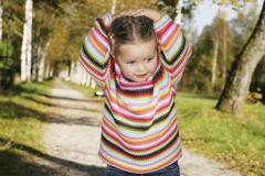 Three-year-old girl holding her hands to her head, earnest Stock Photos