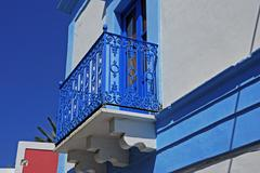 balcony adorned with a bright blue wrought-iron railing, stromboli island, ae - stock photo