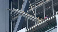 FULL SHOT. Construction worker is directing the movement of a big metal piece.  Stock Footage