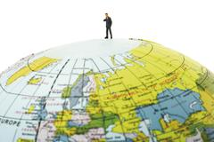 Business executive on top of a globe Kuvituskuvat