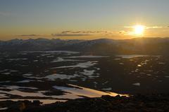 midnight sun shining over a vast, lonely fell landscape, melting snow, abisko - stock photo