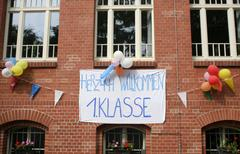 banner, welome first grade students hanging outside a school in berlin, germa - stock photo