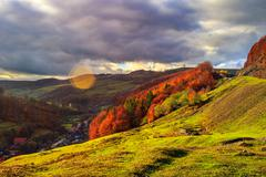 Light  beam falls on hillside with autumn forest in mountain Stock Photos