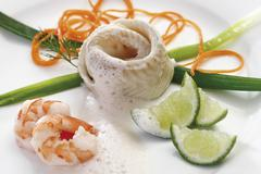Seafood dish: rolled halibut wrapped in a leek bow with leeks, lime wedges, f Kuvituskuvat