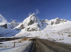 road going through a mountainous winter landscape, lofoten archipelago, norwa - stock photo