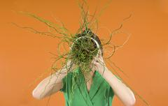 Woman with potted plant in front of her face Stock Photos
