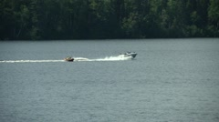Summer Activity - Tubing behind motor boat on beautiful lake Stock Footage