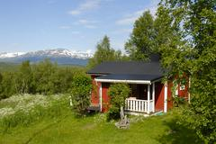 lonely red wooden house amid a pristine landscape near abisko national park,  - stock photo