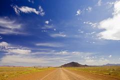 Gravel road leading to arid rocky hills at the edge of the namib desert, nami Stock Photos