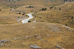 Lonely road winding through the abruzzi landscape, abruzzo, southern italy Stock Photos