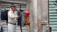 MEDIUM SHOT. Organ grinder, playing the organ in the street.  Stock Footage