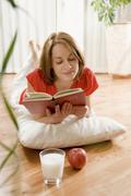 Stock Photo of woman laying on a parquet floor reading a book